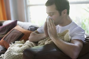 A sick man blowing his nose on the couch