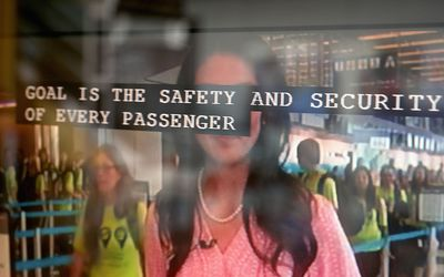 Closed captioning text across a tv screen during a news report about Memorial Day travel