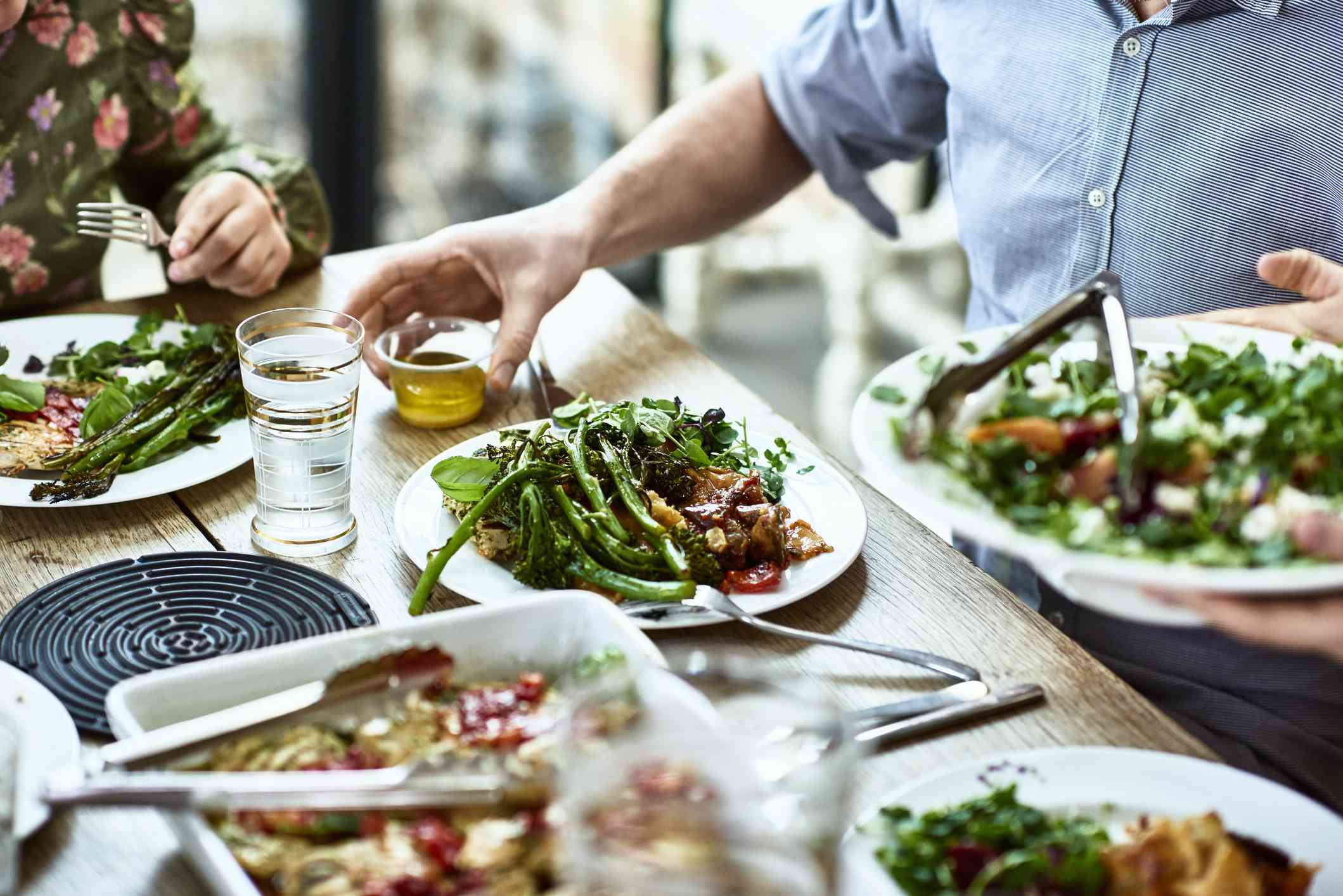 Close up of plates full of greens and tomatoes and people sitting around a table
