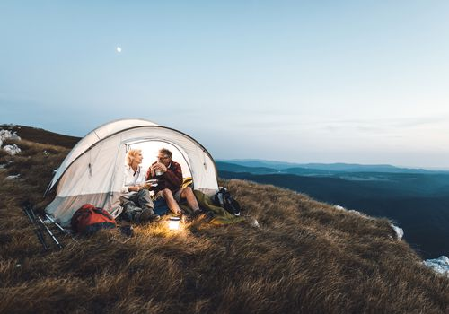 Senior couple camping and eating a snack on a cliff