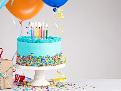 Blue-frosted birthday cake with balloons, a package, and a birthday hat