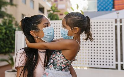 Mom and daughter both wearing face masks.