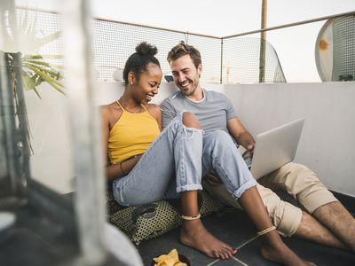 Happy young couple with laptop and earphones sitting on rooftop in the evening