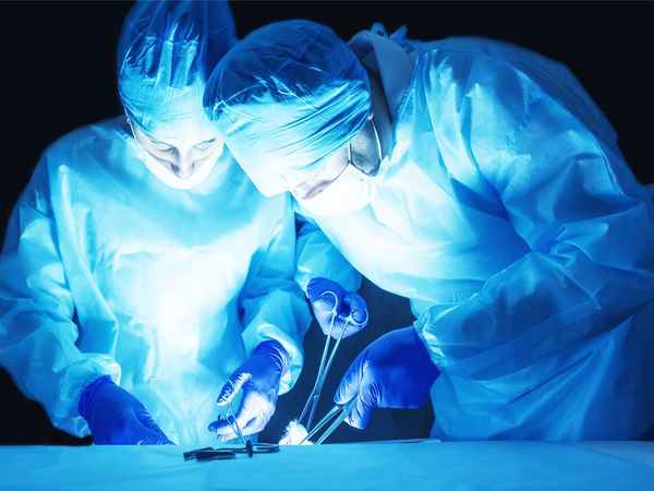 wo surgeons, a man and a woman, perform surgery to remove prostate adenoma and varicocele, fibroadenoma - stock photo
