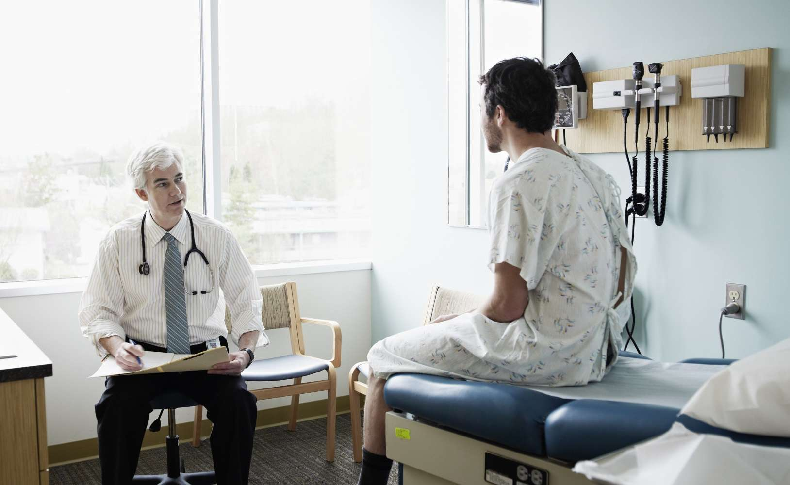 Male patient in discussion with doctor in an examination room.