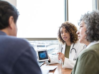 Female neurologist discusses brain scan with patient