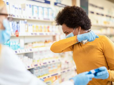 Woman with protection mask and gloves coughing and buying a medicine
