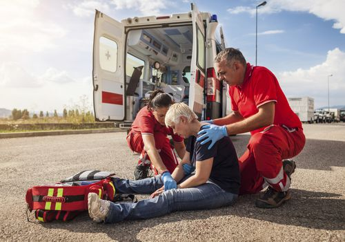 Woman sitting on ground with paramedics
