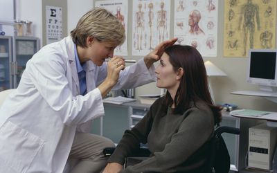a doctor checking a patient's eyes