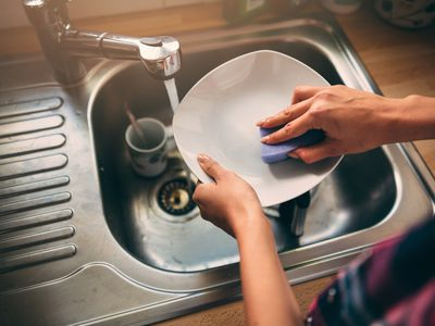 woman cleaning dishes with sponge