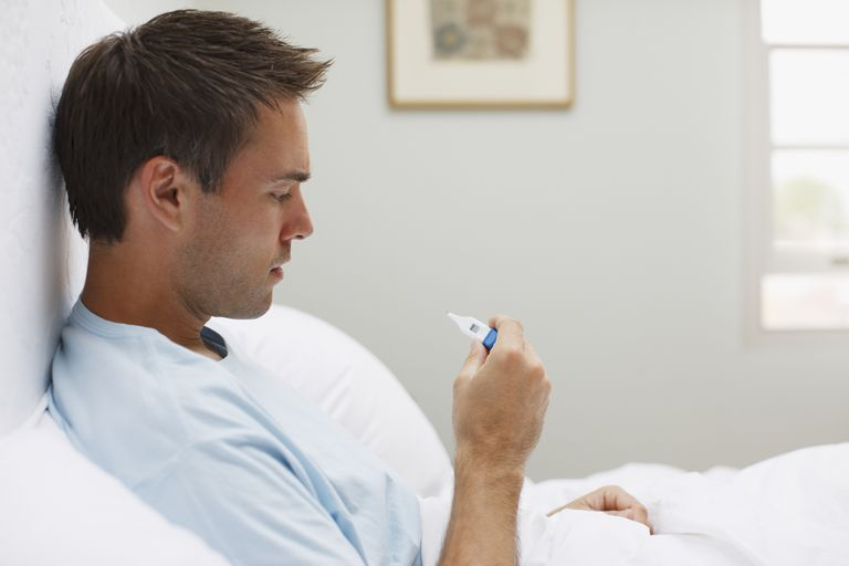 Sick man taking temperature with digital thermometer