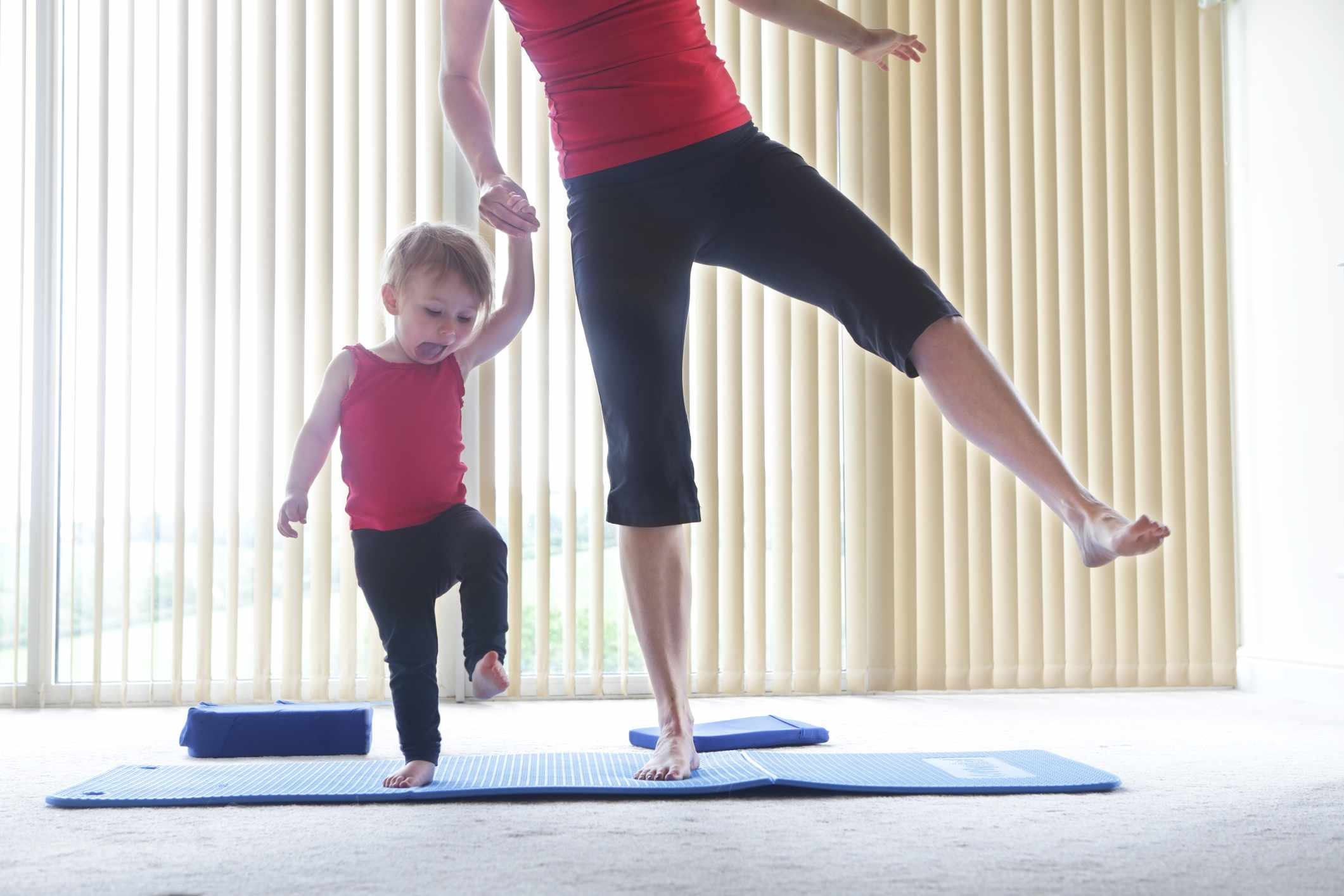 A mother and toddler exercising at home together