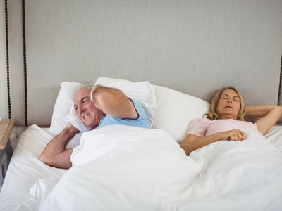Senior man lying on bed and covering his ears with pillow