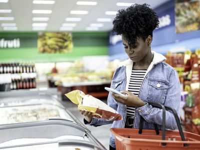 Woman comparing nutrition information on her phone while grocery shopping