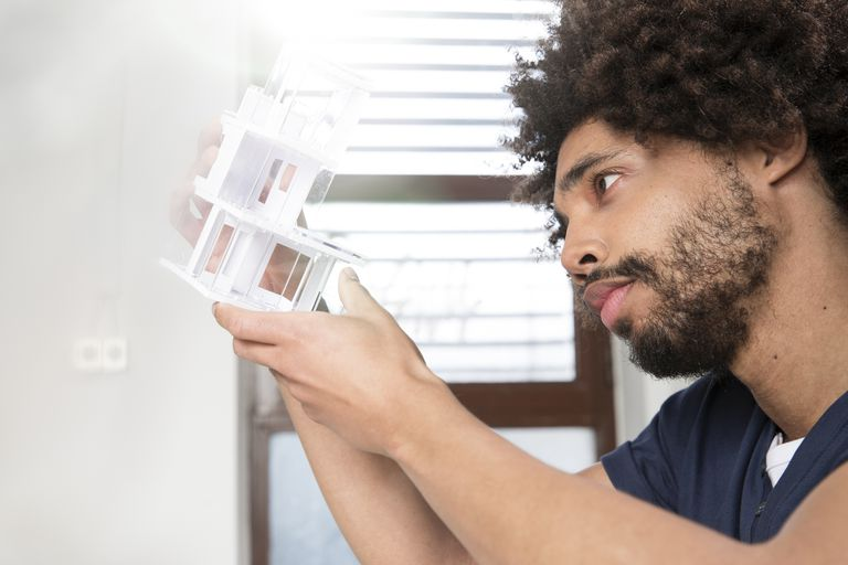 young man looking intensely at an architectural model