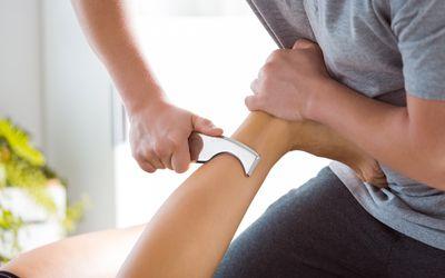 Physiotherapist massaging woman's leg using tools