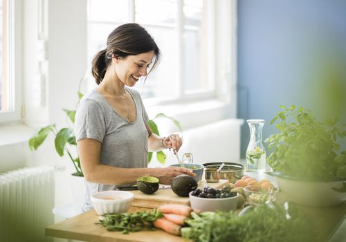Woman preparing healthy food in her kitchen