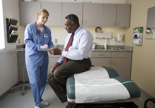Female nurse talking to male patient