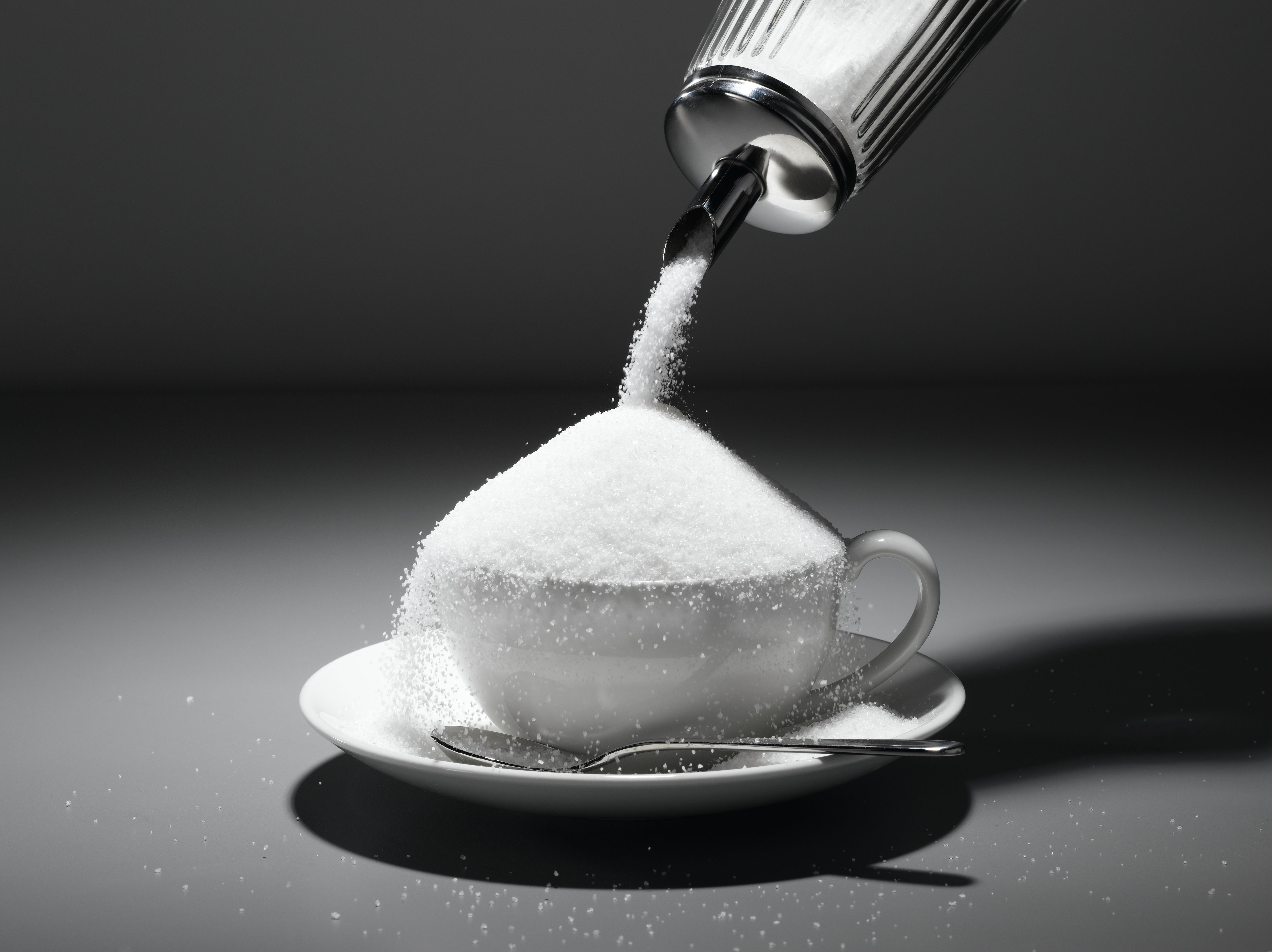 White sugar pouring into cup