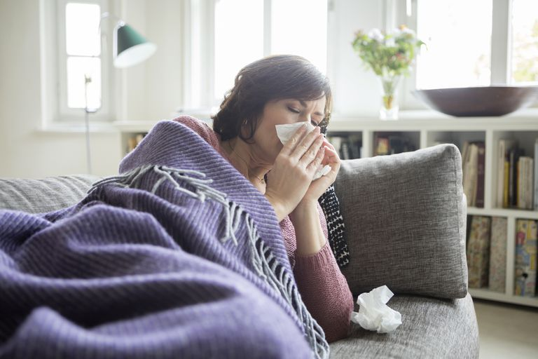 Woman with a cold blowing her nose on a couch