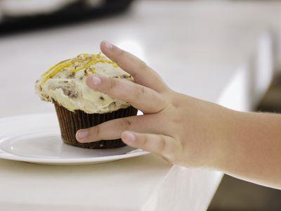 Child reaching for cupcake