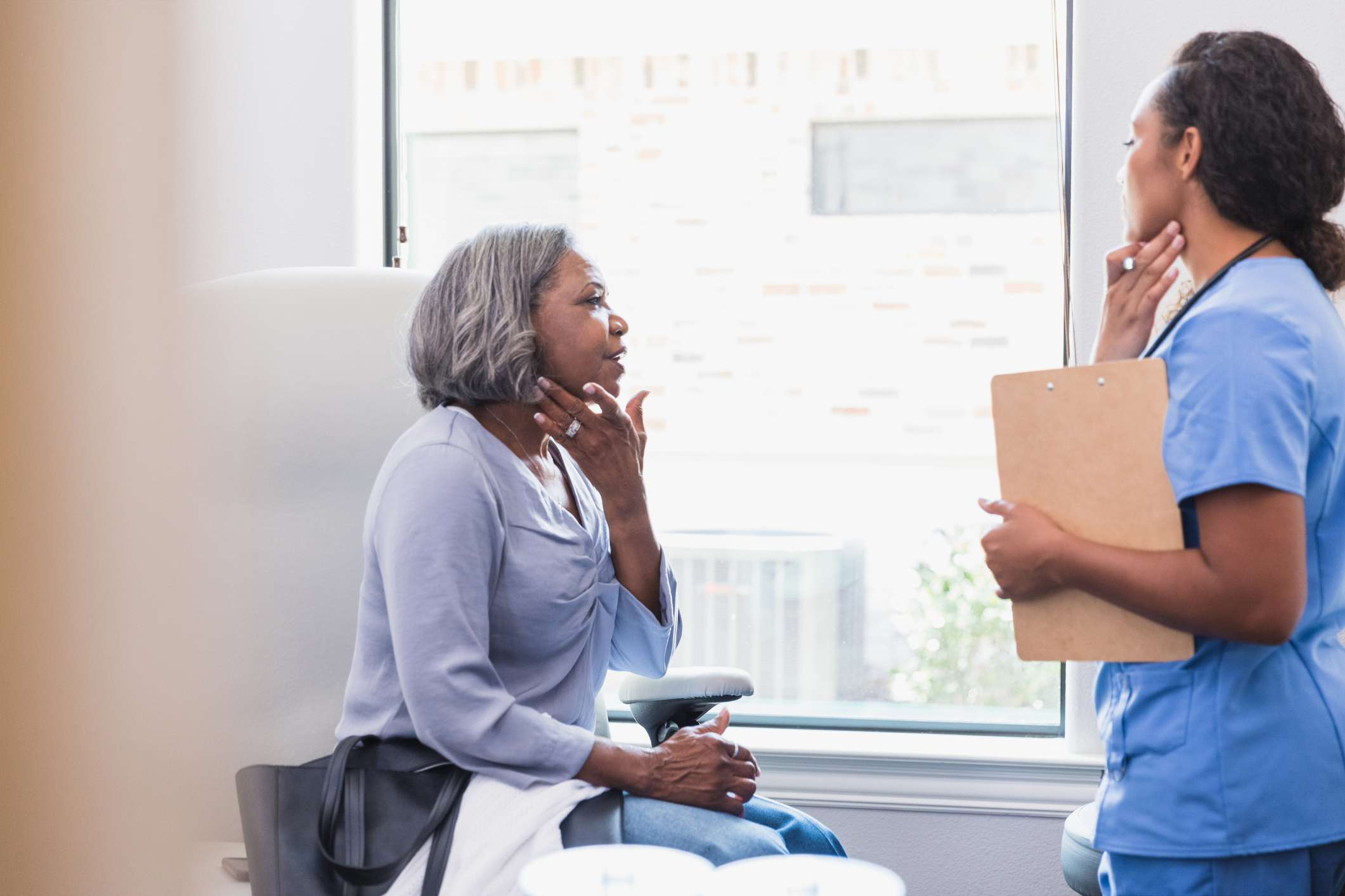 older woman talking to dermatologist