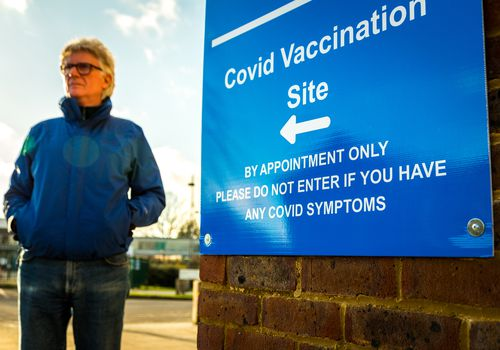 """Close up of a blue sign with white letters that says """"COVID vaccination site by appointment only please do not enter if you have any covid symptoms"""" an older person in a blue jacket is standing to the left of the side but they are not in focus."""