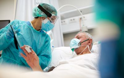 Man with COVID-19 in a hospital bed talking to nurse