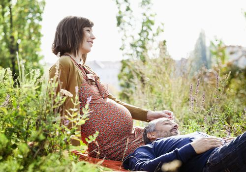 pregnant woman and man relaxing in the nature, she pats him tenderly