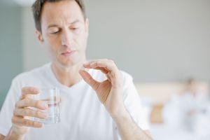 Man taking a pill for hepatitis C