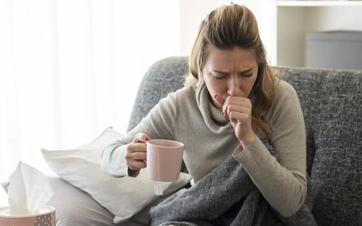 a sick woman coughing at home