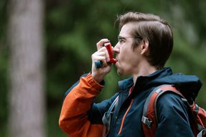 Man wearing backpack outside breathing in with an inhaler