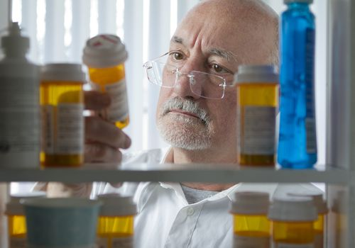 man looking at medicine in pill bottle