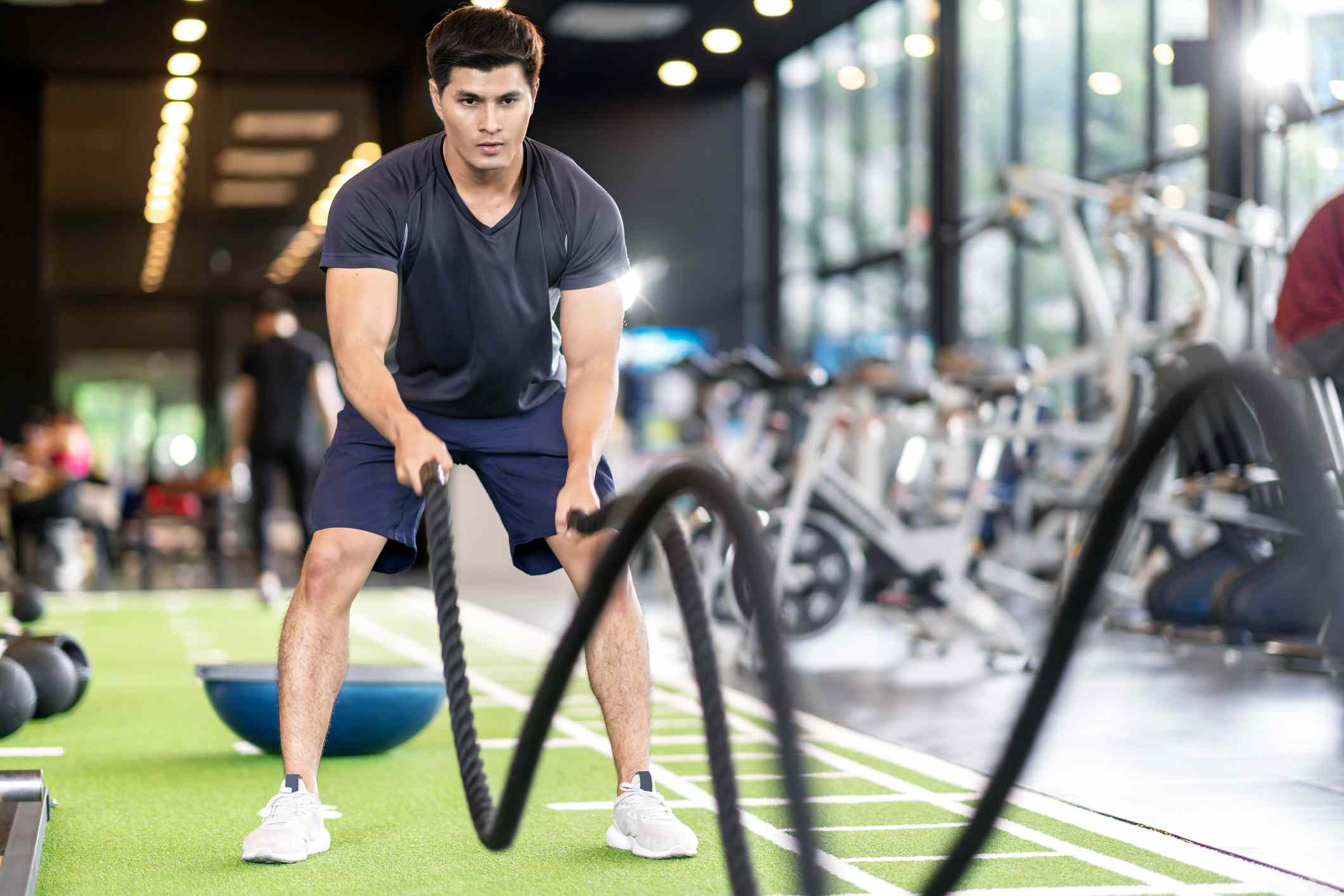 Sporty asian man exercising with battle ropes at the gym on green floor. Strong male determine with her indoor workout for stamina and building muscular body. Athlete battle rope workout concept.