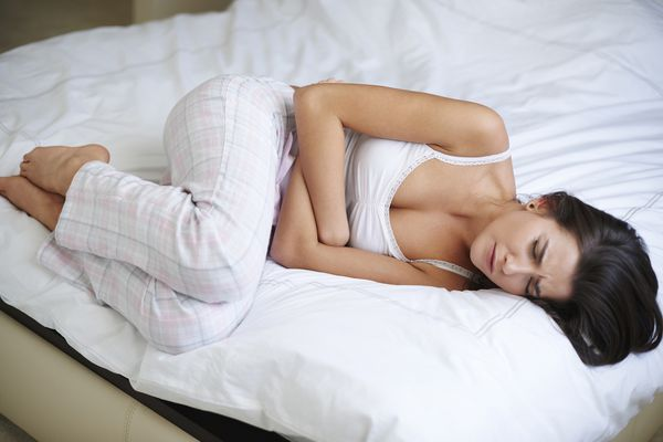 Woman laying on her bed clutching her stomach