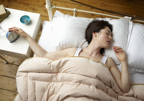 Woman turning off her alarm clock from bed