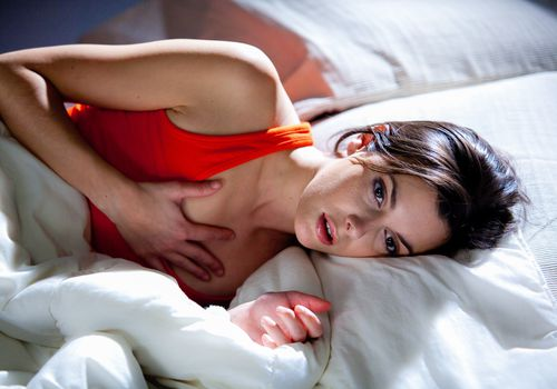 Photo of a woman in bed having trouble breathing