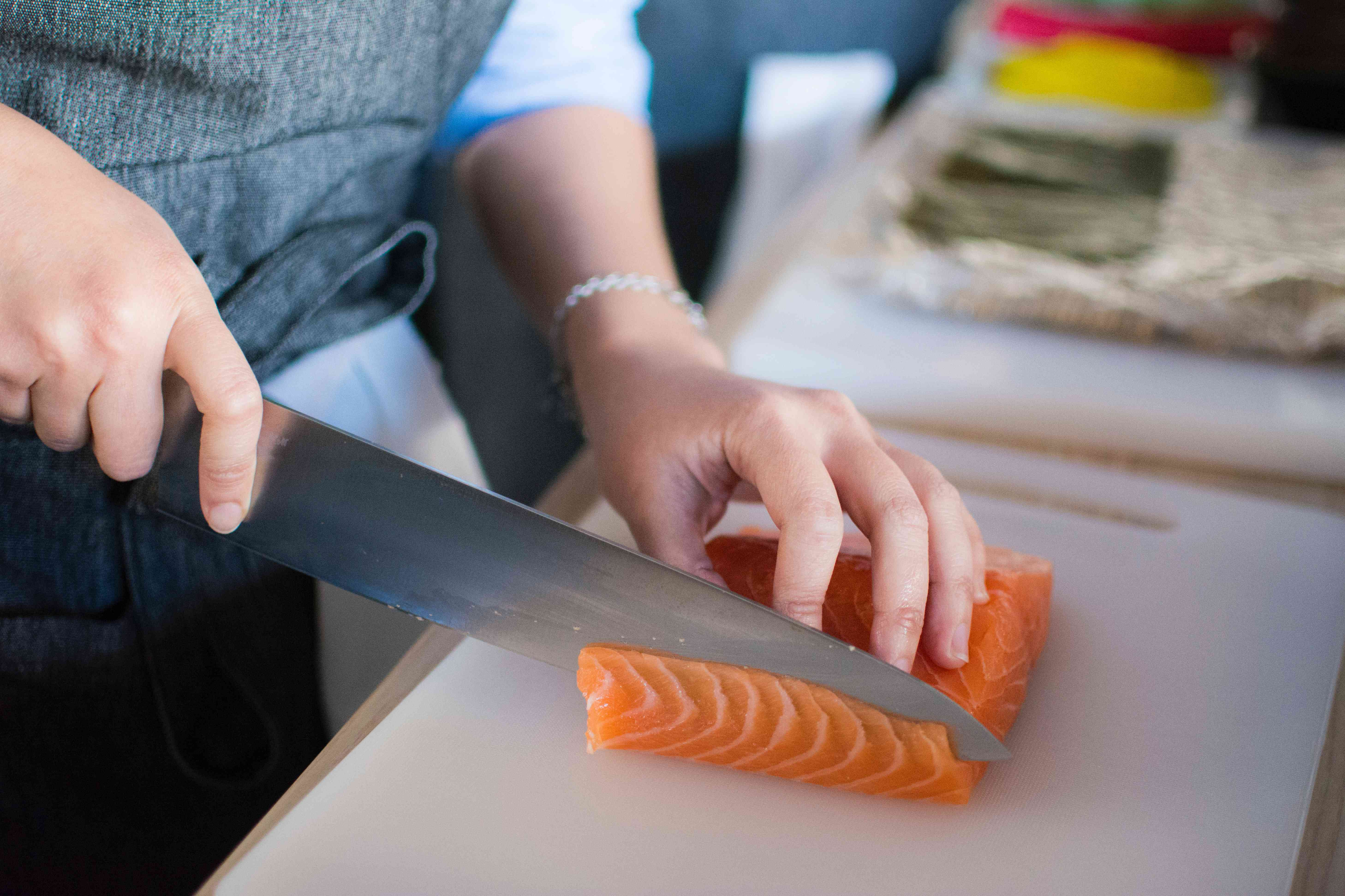 An unseen person cutting salmon with a large knife.