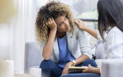 A young woman sits on a couch with her unrecognizable therapist. She puts her head in her hand as she looks out the window with a sad expression. Her therapist puts a hand on her shoulder