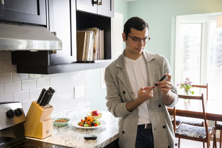 diabetic man checking blood sugar in kitchen before meal