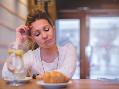 Woman sitting at restaurant table looking down in contemplation at a cup of water, a croissant, and coffee in front of her.