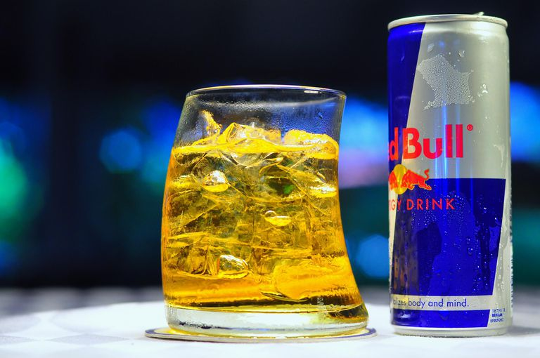 Red Bull energy drink next to a class of gold liquid
