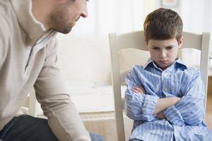 Father sitting next to and looking at displeased son who is 8 or 9 years old