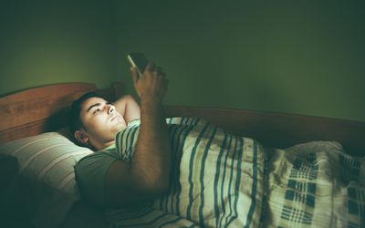 Man using cell phone in bed