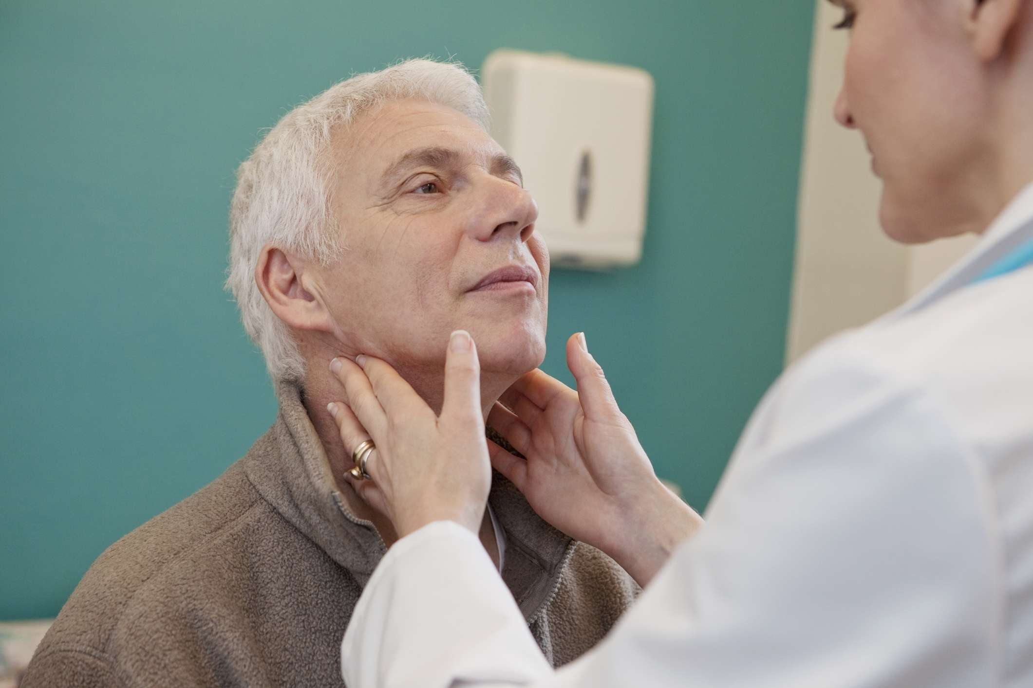 Doctor feeling elderly man's lymph nodes
