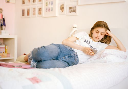 Teen girl looking at her phone on her bed