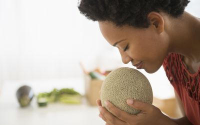Profile of person with short dark hair and brown skin, smelling a melon