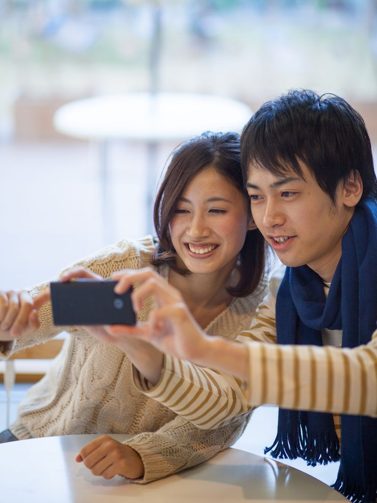 Young couple using a smart phone to take a picture