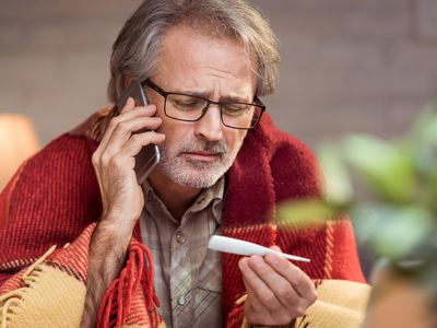 Concerned man looking at thermometer