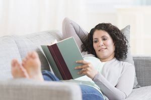 Woman reading a book on the sofa